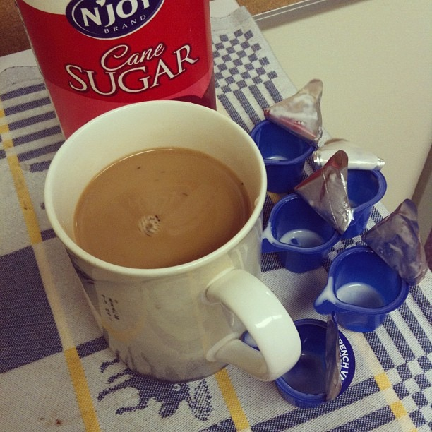 Cup of tea with open cream packets and large sugar container.