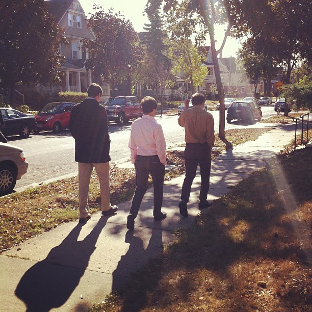 Three young men walking on the sidewalk.
