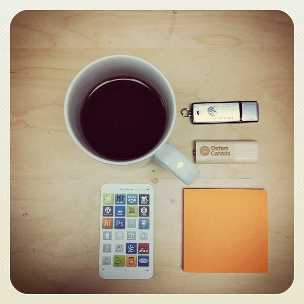 a cup of tea with a few USB drives and a post notpad carefully arranged around it to accompany a haiku