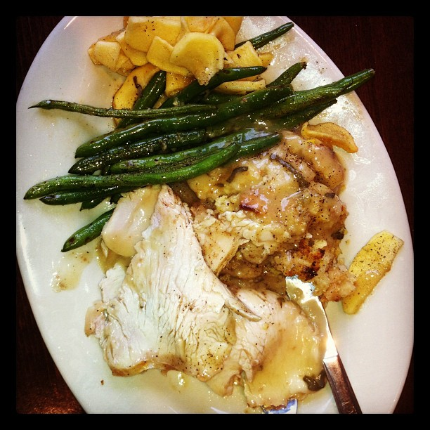 Plate of food: turkey, stuffing, gravy and veggies.
