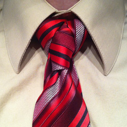 tan shirt with red/orange/black striped tie tied in a cape knot