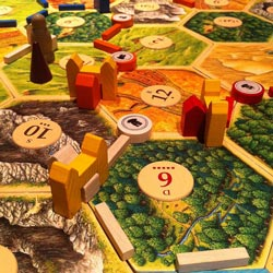 Settlers of Catan game with three cities featured