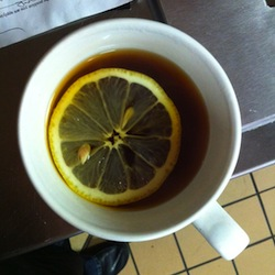 top down view of a mug of tea with a slice of lemon flaoting in it