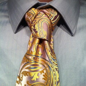 The cape necktie knot, pink/yellow paisly tie on grey shirt