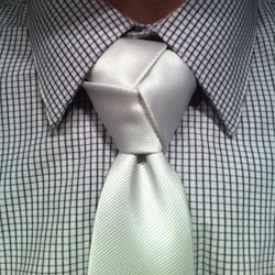 white trinity knot tied over a white and grey pattern shirt