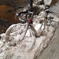 bike covered in snow attached to a pole