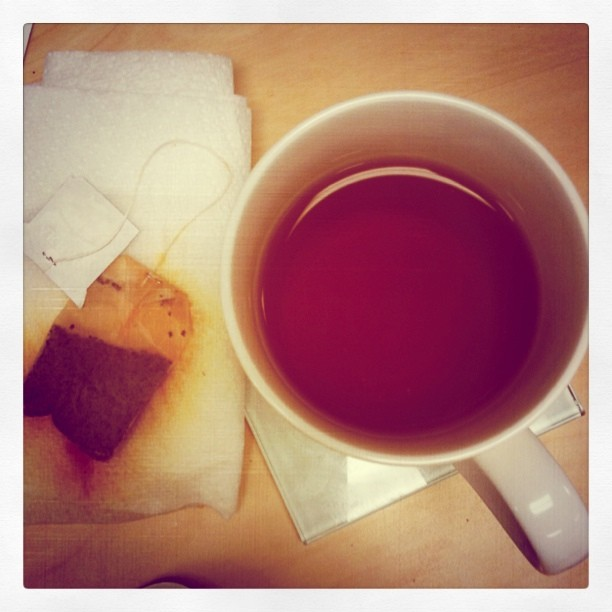 Cup of tea with tea bag on a paper towel next to it.