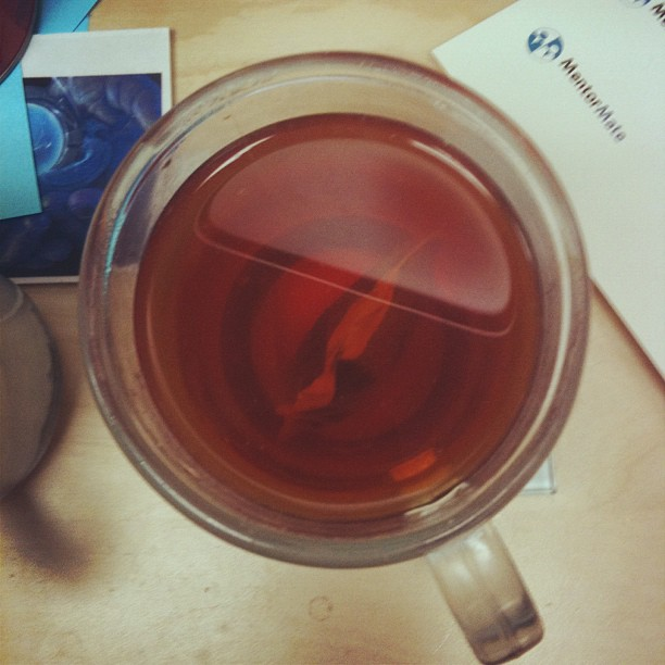 A large cup of tea on a cluttered desk.