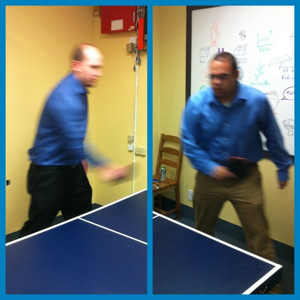 Two guys in blue shirts playing ping pong at the office to accompany a haiku
