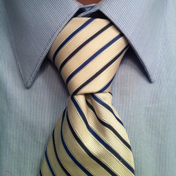 Close up of a white and blue striped tie on a blue shirt, Pratt knot.