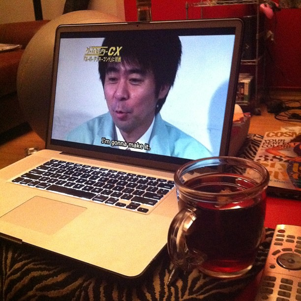 Apple Macbook Pro displaying an episode of gamecenter CX with a cup of tea next to it.