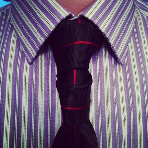 glennie double necktie knot with a www.mentiesshop.com black tie with red verticle stripe